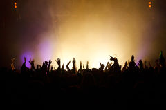 Hands in the air. Silhouetted against great stage lights stock photos