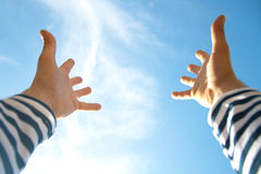 Hands in air across blue sky stock photography