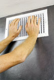 Hands on an Air Vent. Two adult hands placed over an out air vent register of a central heating system on a gray wall near a white ceiling. A white metal air stock photos