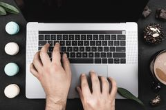 Hands of an amateur of sweets, working on laptop, macarons, cakes and breakfast coffee around. Top view royalty free stock photo