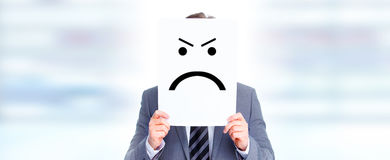 Hands with angry card. Businessman holding paper card with angry face expression Stock Photo