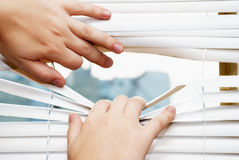 Hands apart on the window blinds Royalty Free Stock Photos
