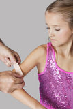 Hands applying adhesive bandage on girl's arm against gray background Stock Photo