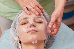 Hands applying collagen facial mask. Face of young woman, cosmetology. Getting rid of acne stock photos