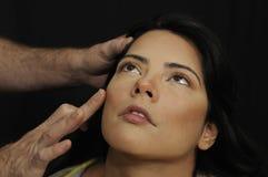 Hands applying make up on hispanic girl Stock Photo
