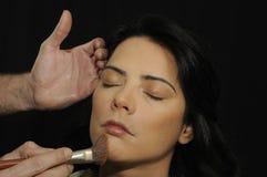 Hands applying make up on hispanic girl Royalty Free Stock Image