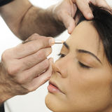 Hands applying make up on hispanic girl Royalty Free Stock Photo