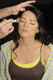 Hands applying make up on hispanic girl Royalty Free Stock Images
