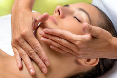 Hands applying neck cream on woman. Stock Image