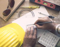 Hands of architect drawing construction plan. On wooden desk Royalty Free Stock Image