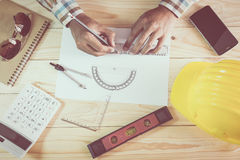 Hands of architect drawing construction plan. On wooden desk Royalty Free Stock Images