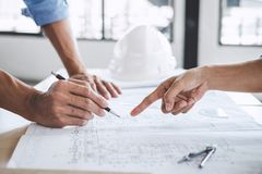 Hands of architect or engineer working on blueprint meeting for. Project working with partner on model building and engineering tools in working site Royalty Free Stock Images
