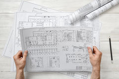 Hands of architect holding a drawing sketch. Workplace of architect. Engineering work. Construction and architecture. Architect drawing. Project Stock Photos