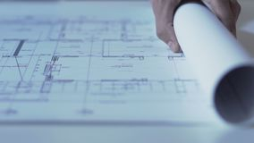 Hands of architect opening drawing of new building guidelines, design bureau. Stock footage stock video