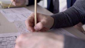 Hands of arctitects checking a building blueprints on the table in the office, close up. Two male professionals are sitting at the wooden desk and correcting stock video footage