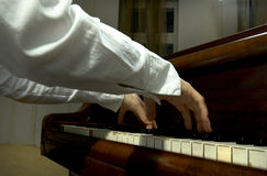 Hands and Arms at the Piano. Close view of the hands and arms of an accomplished and prize winning pianist at the keyboard of a grand piano Royalty Free Stock Photography