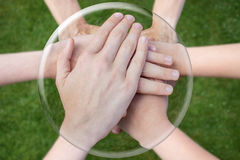 Hands arms uniting in glass sphere. Hands arms uniting in crystal sphere on green grass background stock images