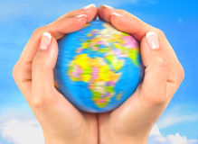 Hands around the world. Hands holding a small globe that is turning against and sky background Royalty Free Stock Photo