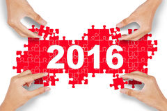 Hands arrange puzzle with numbers 2016 Stock Photo