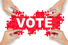 Hands arrange puzzle with vote text Stock Photo