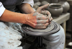 Hands of an artisan. Artisan at his workshop making clay pot Stock Photos