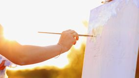 Hands of the artist with a brush, paint a picture on an easel in the open air.  stock footage