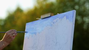 Hands of the artist with a brush, paint a picture on an easel in the open air.  stock video footage