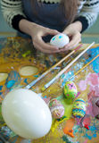 Hands of the artist paint Easter eggs. stock images