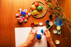 The hands of the artist paint Easter eggs. Watercolor paints in cans and tubes. Handwork. The artist paints Easter religious items. Chicken egg, prepared for royalty free stock photography
