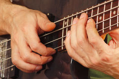 Hands of artist playing the bass guitar close up Stock Photo