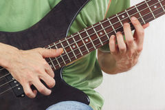 Hands of artist playing the electric bass guitar close up Royalty Free Stock Photography