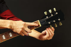 Hands of artist tunes the guitar on dark background. Hands of artist tunes the guitar on a dark background Royalty Free Stock Photo