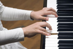 Hands as they press on piano keys. Stock Photos