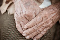 Hands Asian elderly woman grasps her hand on lap, pair of elderly wrinkled hands in prayer sitting alone in his house, World Kind royalty free stock photo