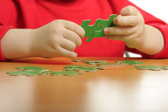 Hands assembling puzzle. Boys hands assembling green pussles laying on a wooden table Stock Image