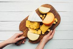 Hands and assorted cheese on wooden board Stock Image