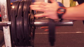 Hands athlete put the weight on the bar stock footage