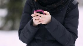 Hands of an attractive young girl with glasses and a red knitted hat picks up a text message using a smartphone. Caucasian woman uses a mobile app in a snow stock video footage