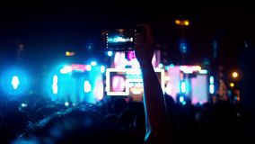 Hands of audience crowd people taking photo with mobile smart phone concert on music festival