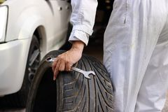 Hands of automotive mechanic in uniform with tire and wrench for fixing car at the repair garage background. Hands of automotive mechanic in uniform with tire Royalty Free Stock Photo