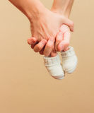 Hands with baby booties. Man and woman hands holding baby booties royalty free stock image