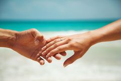 Hands on the background of turquoise water. female hand in male hand stock images
