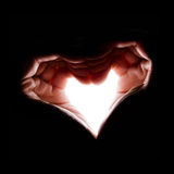 Hands  in backlight make the shape of heart Royalty Free Stock Images