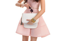 Hands with bag and sunglasses. Woman in light salmon dress. Dark sunglasses and white purse. Expensive jewelry with watch Stock Photos