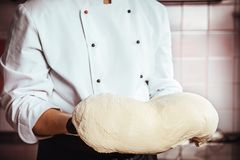 Hands of the Baker knead layer of dough on kitchen background. the working process concept. Male baker holds dough. royalty free stock image