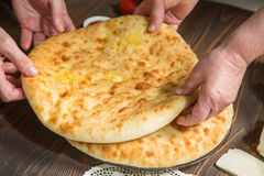 Hands of bakers are keeping Ossetian pies Royalty Free Stock Photography
