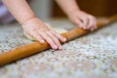 Hands baking dough with rolling pin on table. little chef bake in kitchen. Stock Image