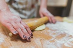 Hands baking dough with rolling pin on wooden table. Bake Royalty Free Stock Images