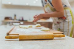 Hands baking dough with rolling pin on wooden table. Bake Stock Photography