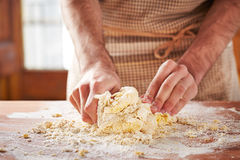 Hands baking dough on wooden table Stock Image